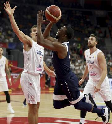 United States' Kemba Walker trips as he tries to shoot past Serbia's Bogdan Bogdanovic at left during a consolation playoff game for the FIBA Basketball World Cup in Dongguan in southern China's Guangdong province on Thursday, Sept. 12, 2019. (AP Photo/Ng Han Guan)