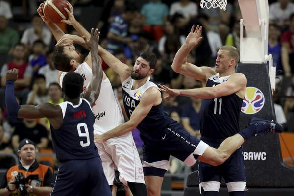 Serbia's Nikola Milutinov keeps the ball away from United States' Jaylen Brown, left, United States' Joe Harris, center and United States' Mason Plumlee at right during a consolation playoff game for the FIBA Basketball World Cup in Dongguan in southern China's Guangdong province on Thursday, Sept. 12, 2019. (AP Photo/Ng Han Guan)