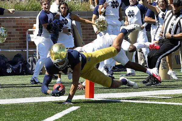 Notre Dame defensive back Kyle Hamilton dives into the end zone after returning an interception 32 yards in the first quarter of Saturday's game.