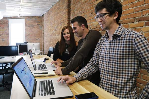 Associated Press  Shane Griffiths, right, and Trenton Erker, center, are co-owners of the digital marketing company Clarity Online. They uses technology to take care of billing and scheduling appointments.