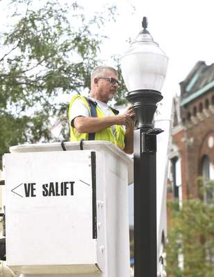 Michelle Davies | The Journal Gazette Rick Hertig, who works for the city's Street Light Engineering division,  replaces a lamppost Monday morning that had been knocked down at  Wayne and Calhoun streets.