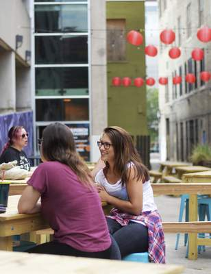 Katie Fyfe | The Journal Gazette Ashton Monroe chats with friends Monday afternoon in  Half Pint Alley, outside 816 Pint & Slice. Tables and lights were added to the downtown alley this summer.
