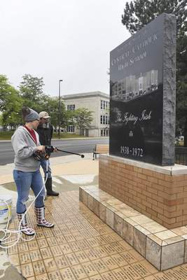 Michelle Davies | The Journal Gazette Michael Rennecker of North West Granite Works and his daughter Carrie  clean efflorescence  off the brick of the Central Catholic High School memorial at  Clinton and Lewis streets on Tuesday morning. Efflorescence is a crystalline deposit of salts found on brick, concrete and stone.
