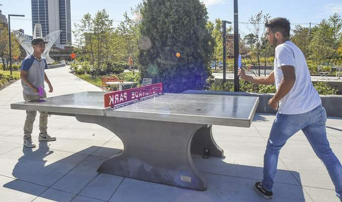 Michelle Davies | The Journal Gazette Eh Moo Seet, left, and Ricardo Lopez, both from Fort Wayne, enjoy a game of pingpong during their first visit to Promenade Park on Wednesday afternoon.