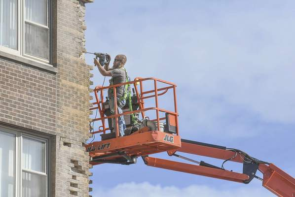 Michelle Davies | The Journal Gazette Tom Ketterling with Carrington Masonry works on replacing bricks on the Westberry Apartments building downtown Thursday morning.