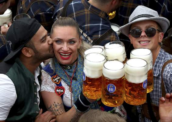 Associated Press A waitress is kissed by a guest as she holds glasses of beer during the opening of the 186th Oktoberfest on Saturday in Munich.