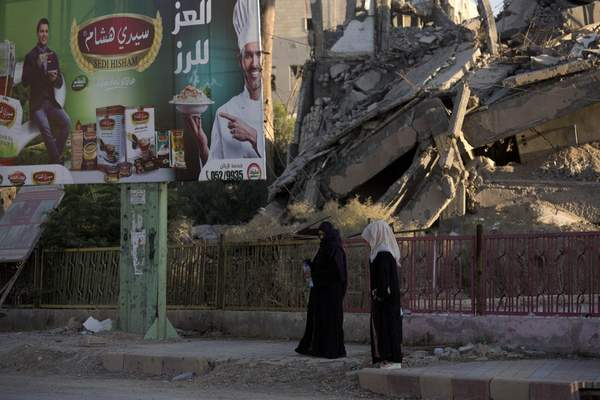 In this Thursday, Sept. 5, 2019, photo, two women walk past a billboard and a destroyed building in al-Naim square, used by Islamic State militants for execution during their rule, in Raqqa, Syria. (AP Photo/Maya Alleruzzo)