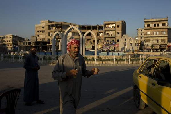In this Thursday, Sept. 5, 2019, photo, a truck driver takes a tea break in al-Naim square, used by Islamic State militants for execution during their rule, in Raqqa, Syria. It is now renamed Freedom square. (AP Photo/Maya Alleruzzo)