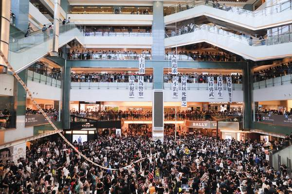 Protesters grab queuing tickets hanging from several floors above issued by a restaurant owned by a pro-Beijing company inside a shopping mall at the Sha Tin district in Hong Kong Sunday, Sept. 22, 2019. (AP Photo/Kin Cheung)