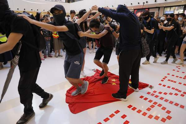 Protesters walk on a Chinese national flag during a protest at a mall in Hong Kong on Sunday, Sept. 22, 2019. Hong Kong's pro-democracy protests, now in their fourth month, have often descended into violence late in the day and at night. A hardcore group of protesters says the extreme actions are needed to get the government's attention. (AP Photo/Kin Cheung)