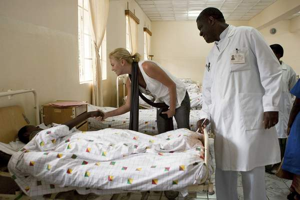 In this March 30, 2009, photo provided by the United Nations, Dr. Denis Mukwege, right, director of Panzi Hospital, stands by actress and U.N. Ambassador for Peace, Charlize Theron, as she visits the hospital in Bukavu, South Kivu, Congo. (Marie Frechon/The United Nations via AP)