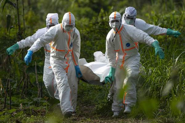 FILE - In this Sunday, July 14 fike, 2019 photo, burial workers dressed in protective gear carry the remains someone that died of Ebola, in Beni, Congo. (AP Photo/Jerome Delay)