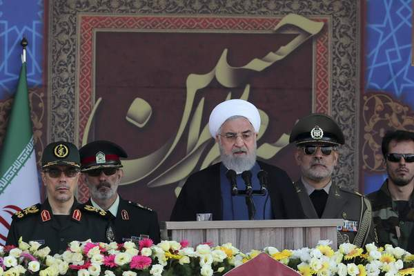 In this photo released by the official website of the office of the Iranian Presidency, President Hassan Rouhani speaks at a military parade marking 39th anniversary of outset of Iran-Iraq war, in front of the shrine of the late revolutionary founder Ayatollah Khomeini, just outside Tehran, Iran, Sunday, Sept. 22, 2019.  (Iranian Presidency Office via AP)