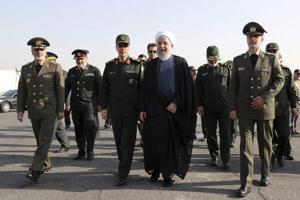 In this photo released by the official website of the office of the Iranian Presidency, President Hassan Rouhani, center, arrives for a military parade ceremony marking 39th anniversary of outset of Iran-Iraq war, as he is accompanied by commanders of armed forces in front of the shrine of the late revolutionary founder Ayatollah Khomeini, just outside Tehran, Iran, Sunday, Sept. 22, 2019. (Iranian Presidency Office via AP)