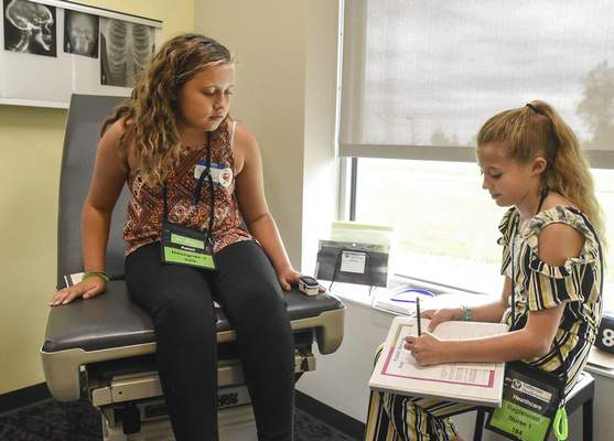Michelle Davies   The Journal Gazette  Avilla Elementary fifth grader Cailyn Lash, right, does a heath examination on classmate Zaylee Davies, left, in the Lutheran Health Network room at Junior Achievement of Northern Indiana Wednesday afternoon.