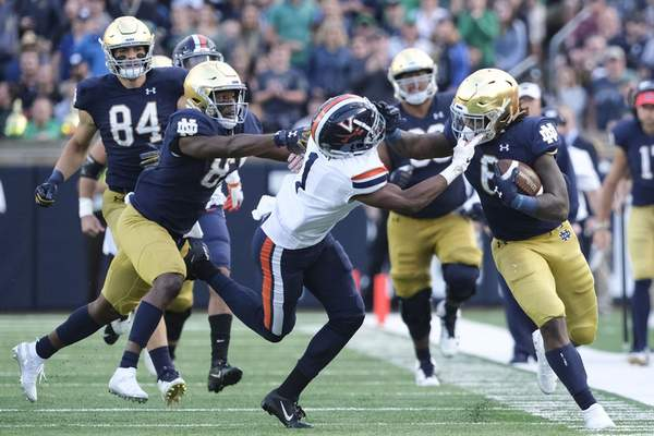 Notre Dame running back Tony Jones Jr. fends offa would-be Virginia tackler in the second half of Notre Dame's 35-20 win over the Cavaliers on Saturday. Jones had a career-high 131 rushing yards and three touchdowns.(AP Photo/AJ Mast)