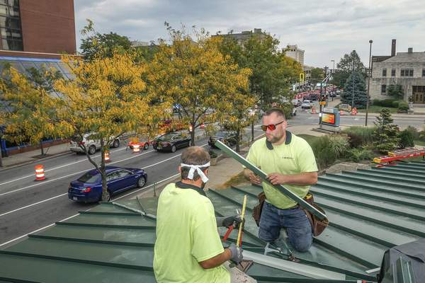 Mike Moore | The Journal Gazette Metal workers Jerad Elett, right, and Mark Schmitz with C.M.S. Roofing work Wednesday on the roof over Foellinger-Freimann Botanical Conservatory's hallway extension project. The project will link the conservatory to Embassy Theatre next door.