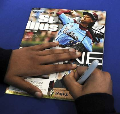 FILE - In this Saturday, Feb. 27, 2016 file photo, Mo'ne Davis, 14, of Philadelphia, signs an autograph for a fan on the cover of Sports Illustrated magazine at PNC Field in Moosic, Pa. Little-known media company Maven, Sports Illustrated's new manager, says the sports magazine is cutting more than 40 jobs out of a staff of 150. Maven spokesman Greg Witter says it will add 200 contractors to cover college and professional sports teams for Sports Illustrated. Maven struck a licensing deal to operate Sports Illustrated with the magazine's new owner, branding company Authentic Brands Group, in June. (Butch Comegys/The Times-Tribune via AP, File)