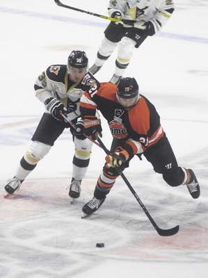 Katie Fyfe | The Journal Gazette  The Komets' Matthew Boudens chases the puck during the first period against the Wheeling Nailers at Memorial Coliseum on Saturday.