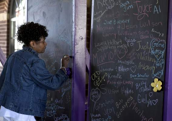 Rachel Von Stroup | The Journal Gazette  Pamela Martin writes the name of her mother Maureen A. Martin on a board honoring those who have Alzheimer's or who died from the diseaseas part ofthe 2019 Walk to End Alzheimer's at Parkview Field on Saturday.