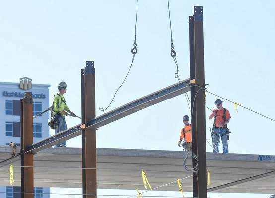 Michelle Davies | The Journal Gazette Workers stand high above the ground at the construction site of the boutique hotel at Main and Harrison streets Tuesday afternoon. The project is expected to be finished by late next year.