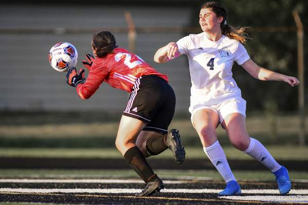 Mike Moore | The Journal Gazette Concordia goalkeeper Katelyn Faherty makes the save in front of Bishop Dwenger forward Mackenzie Guzhnay in the first half of their sectional opener Tuesday at Leo. The No. 9 Saints ousted the No. 16 Cadets from the postseason.