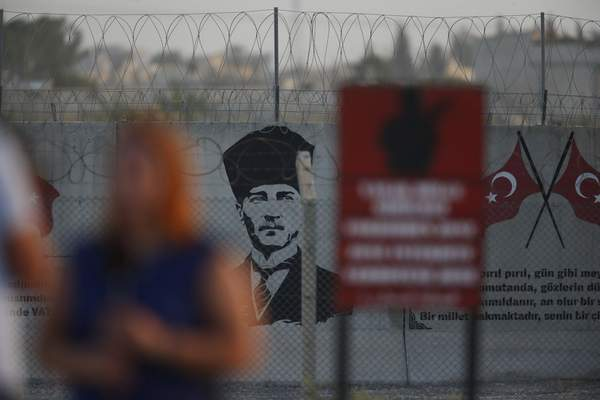 A graffiti of modern Turkey's founder Mustafa Kemal Ataturk is seen on the Turkish side of the border between Turkey and Syria, as a TV journalist works in Akcakale, Sanliurfa province, southeastern Turkey, Tuesday, Oct. 8, 2019. The Turkey - Syria border has became a hot spot as Turkish Vice President Fuat Oktay said Turkey was intent on combatting the threat of Syrian Kurdish fighters across its border in Syria.(AP Photo/Lefteris Pitarakis)