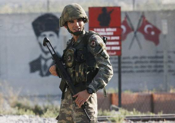 Shortly after the Turkish operation inside Syria had started, a Turkish soldiers stands at the border with Syria in Akcakale, Sanliurfa province, southeastern Turkey, Wednesday, Oct. 9, 2019. Turkey launched a military operation Wednesday against Kurdish fighters in northeastern Syria after U.S. forces pulled back from the area, with a series of airstrikes hitting a town on Syria's northern border.(AP Photo/Lefteris Pitarakis)