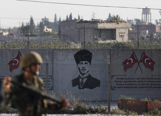 Shortly after the Turkish operation inside Syria had started and backdropped by a graffiti of modern Turkey's founder Mustafa Kemal Ataturk, a Turkish soldier stands on the Turkish side of the border in Akcakale, Sanliurfa province, southeastern Turkey, Wednesday, Oct. 9, 2019. (AP Photo/Lefteris Pitarakis)