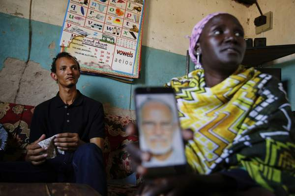 Gerald Erebon sits with his aunt, Scolastica Apayo, as she holds a phone displaying a photo of the Rev. Mario Lacchin, during an interview at her home in the Isiolo area of the Archers Post settlement in Kenya on Sunday, June 30, 2019. (AP Photo/Brian Inganga)