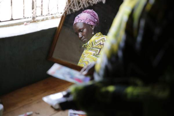 Scolastica Apayo, sister of the late Sabina Losirkale, looks through her old photos in the Isiolo area of the Archers Post settlement in Kenya on Sunday, June 30, 2019. (AP Photo/Brian Inganga)