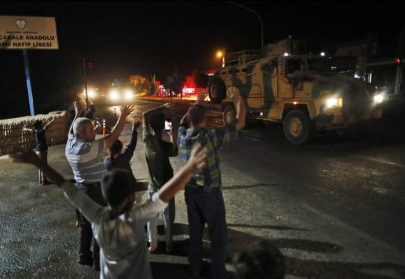 Local residents jeer and applaud as a convoy of Turkish forces vehicles and trucks carrying tanks and armoured personnel carriers is driven in Sanliurfa province, southeastern Turkey, Tuesday, Oct. 8, 2019. (AP Photo/Lefteris Pitarakis)