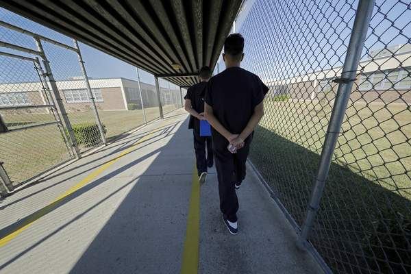 Detainees walk with their hands clasped behind their backs along a line painted on a walkway inside the Winn Correctional Center in Winnfield, La., Thursday, Sept. 26, 2019. (AP Photo/Gerald Herbert)