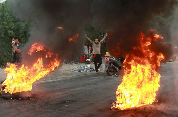 FILE - In this Sunday, Oct. 6, 2019 file photo, anti-government protesters set fires and close a street during a demonstration in Baghdad, Iraq. (AP Photo/Khalid Mohammed, File)