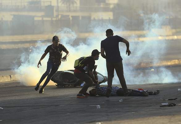 FILE - In this Oct. 5, 2019 file photo, anti-government protesters rush to an injured protester during a demonstration in Baghdad, Iraq. (AP Photo/Hadi Mizban, File)