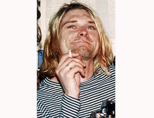 FILE - This 1993 file photo shows Kurt Cobain, the lead singer of the U.S. rock band Nirvana. A custom made Fender guitar and olive green cardigan sweater owned by Cobain are among the rock and roll items up for auction on Oct. 25 and 26. (AP Photo/Mark J. Terrill, File)