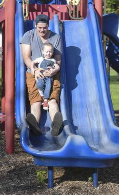 Michelle Davies | The Journal Gazette Sunny Strack, 2, goes down the slide Wednesday morning at Northside Park in the arms of his father, Chris Strack.