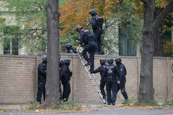 Associated Press Police officers cross a wall at a crime scene in Halle, Germany, on Wednesday after a shooting that left two people dead.