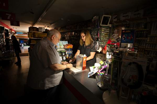 Associated Press Tom Hyde, left, buys a can of fuel for his Coleman camp stove from Kim Scheffer at a Village True Value Hardware store in Santa Rosa, Calif., on Wednesday amid power outages over wildfire fears.