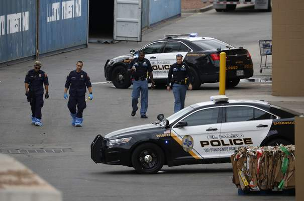 FILE - In this Tuesday, Aug. 6, 2019 file photo, police officers walk behind a Walmart at the scene of a mass shooting at a shopping complex, in El Paso, Texas. (AP Photo/John Locher, File)