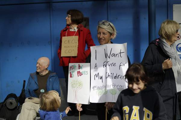 An Extinction Rebellion climate change protester holds placards during a demonstration outside City Airport in London, Thursday, Oct. 10, 2019. (AP Photo/Matt Dunham)