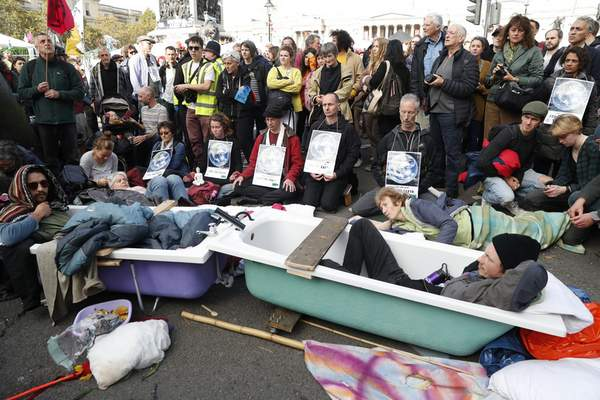 Climate change protesters lie in to joined bathtubs as the demonstrate in Trafalgar Square in London, Thursday, Oct. 10, 2019. (AP Photo/Alastair Grant)