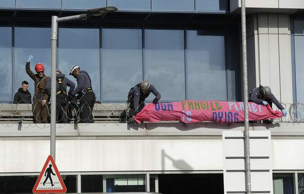 Police officers wearing safety equipment remove an Extinction Rebellion demonstrator, left in red helmet, and a banner after he occupied a raised area at City Airport in London, Thursday, Oct. 10, 2019. (AP Photo/Matt Dunham)