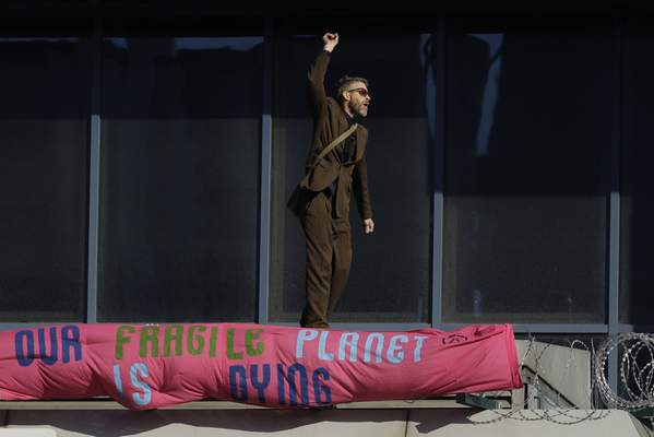 An Extinction Rebellion demonstrator gestures with a banner as he occupies a raised area at City Airport in London, Thursday, Oct. 10, 2019. (AP Photo/Matt Dunham)