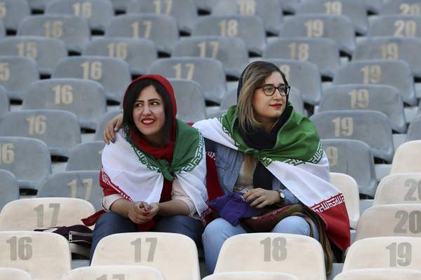 Iranian women wear their country's flag on their shoulders at the Azadi Stadium for the 2022 World Cup qualifier soccer match between Iran and Cambodia, in Tehran, Iran, Thursday, Oct. 10, 2019. Iranian women were freely allowed into the stadium for the first time in decades. (AP Photo/Vahid Salemi)