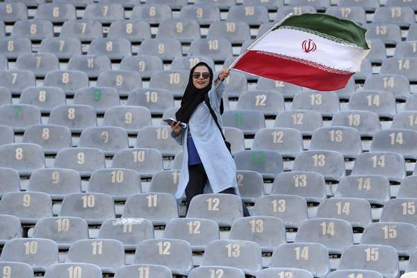 An Iranian woman waves her country's flag as she arrives at the Azadi Stadium to watch the 2022 World Cup qualifier soccer match between Iran and Cambodia, in Tehran, Iran, Thursday, Oct. 10, 2019. (AP Photo/Vahid Salemi)