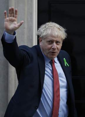 Britain's Prime Minister Boris Johnson waves to the media from the doorstep of 10 Downing Street in London, Thursday, Oct. 10, 2019, ahead of meeting mental health campaigners. (AP Photo/Alastair Grant)