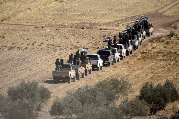 Turkey-backed FSA fighters are heading toward Syrian town of Tal Abyad from Turkish border town of Akcakale, Turkey, Thursday, Oct. 10, 2019. (DHA via AP)
