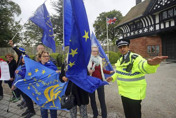 Associated Press A police officer talks to anti-Brexit protesters outside  Thornton Manor, in The Wirral, England, on Thursday.