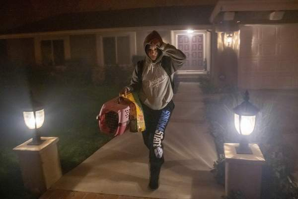 A woman evacuates her home with her cat as the Saddleridge fire threatens homes in Granada Hills, Calif., Friday, Oct. 11, 2019. (AP Photo/Michael Owen Baker)